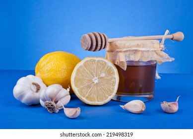 Composition of honey, lemon and garlic blue background.