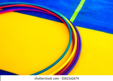 Composition with hoops and mat on wooden background in gym.