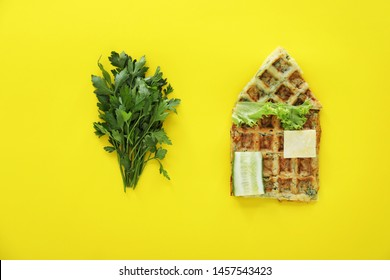 Composition with house made of squash waffles and parsley on color background