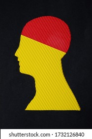 The composition of human head shaped from paper cut with red and yellow color paper as a background. Copy space