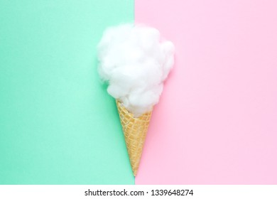 Composition of ice cream cone with pink wisp of bast on a light blue background. Bathroom cosmetic accessories. Flat Lay. Top View