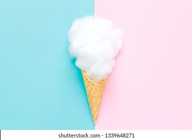 Composition of ice cream cone with white cotton wool on a light blue, pink  background. Bathroom cosmetic accessories. Flat Lay. Top View