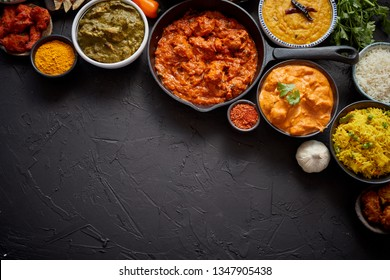 Composition of Indian cuisine in ceramic bowls on black stone table. Tikka masala, butter chicken, Nilgiri, seekh kebab, rice, Onion Bhajia, paneer, samosa, naan, Daal Tarka, spices With copy space