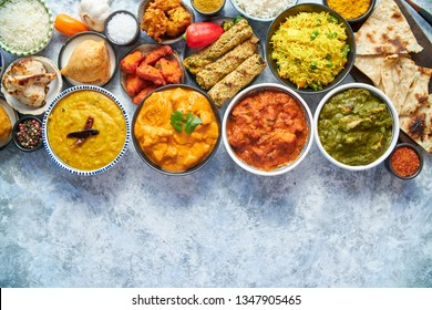 Composition of Indian cuisine in ceramic bowls on stone table. Tikka masala, butter chicken, Nilgiri, seekh kebab, rice, Onion Bhajia, paneer, samosa, naan, Daal Tarka, spices With copy space