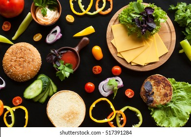 The composition of the ingredients for a burger on a black background. Appetizing picture about delicious food