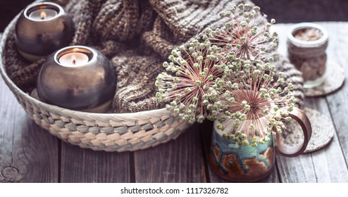 Composition in the interior with a cup and candles on a wooden table