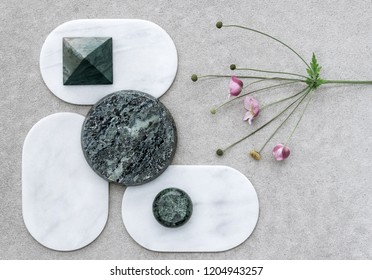 Composition with Japanese anemone and various marble shapes.