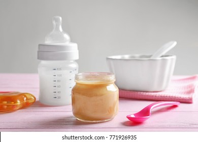 Composition with jar of healthy baby food on wooden table