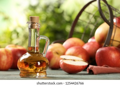 Composition with jug of apple vinegar on table. Space for text
