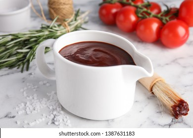 Composition with jug of barbecue sauce on marble table