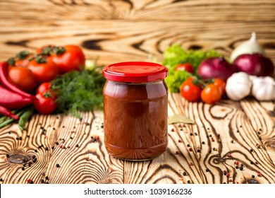 Composition of ketchup (tomato paste) in jar and ingredients on wooden background
