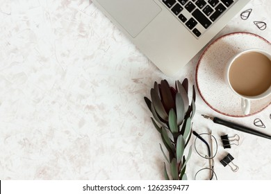 Composition with laptop, mug of coffee, leucadendron flower, stationery and accessories on a beige textured background