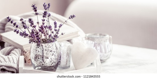 composition with lavender in a beautiful glass on the table in the living room, the concept of home comfort