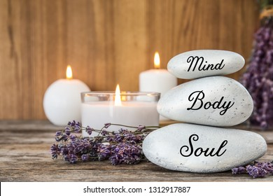 Composition of lavender flowers and zen stones with words Mind, Body, Soul on table against  wooden background. Space for text