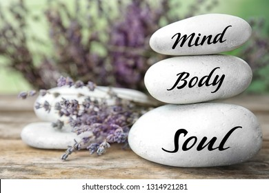 Composition of lavender flowers and zen stones with words Mind, Body, Soul on table against blurred background. Space for text