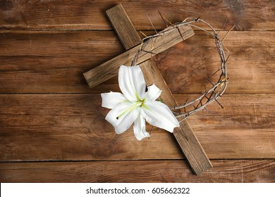 Composition with lily, crown of thorns and cross on wooden background