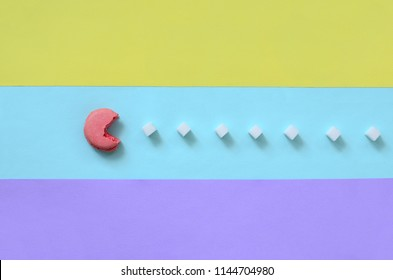 A composition of macaroon with an open mouth that is going to eat sugar cubes on a blue, pink, yellow and violet pastel background. The concept of old video games