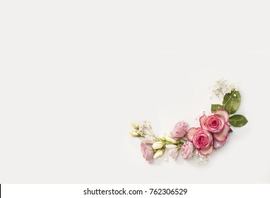 Composition made from roses and decorative addons, shaped in frame, flat lay, top view.