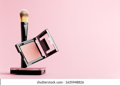 Composition with makeup items on a white background. Black brush, makeup tool, packing of rouge and powder levitate on a pastel backdrop. Set of beauty products for face, lips and eyes with copy space