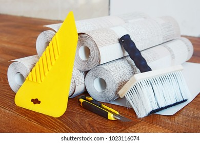 Composition with many rolls of wallpaper and tools for wallpapering