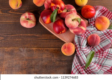 a composition from many varieties of peach on a cutting board on a brown wooden background with a place for an inscription. Top view