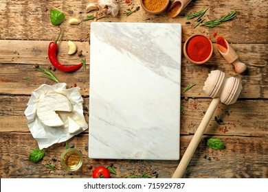Composition with marble board and ingredients for cooking on wooden background