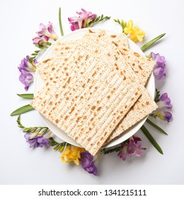 Composition of matzo and flowers on light background, top view. Passover (Pesach) Seder