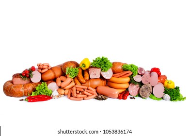 Composition from meat products. Decorated with vegetables and leaves of green salad. Boiled sausages in natural shell. Isolated on white background