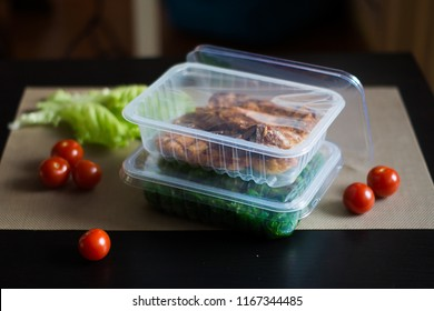 Composition with meat and salad in plastic sealed tray with tomatoes on a dark table