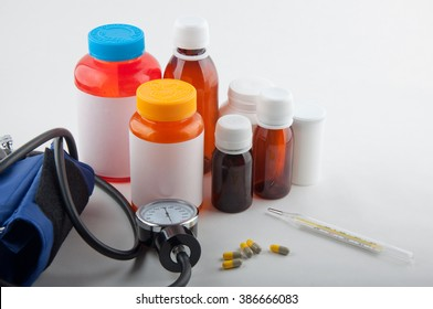 Composition of medical thermometer, tonometer, pills and colorful bottles for tablets on white background