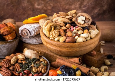 Composition from mix of dried fruits and nuts - symbols of judaic holiday Tu Bishvat. Brown background, close up
