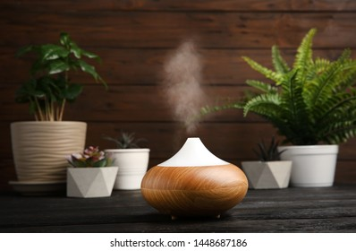 Composition with modern essential oil diffuser on black wooden table against brown background, space for text