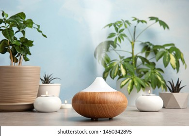 Composition with modern essential oil diffuser on table against blue background, space for text