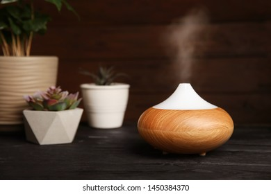 Composition with modern essential oil diffuser on black wooden table against dark background, space for text