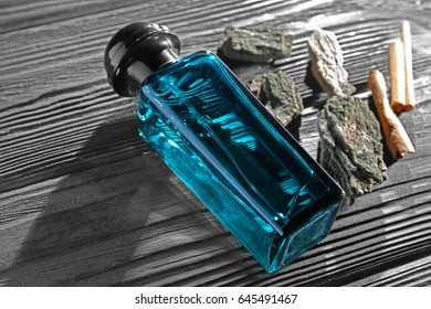 Composition with modern male perfume on dark wooden background, closeup
