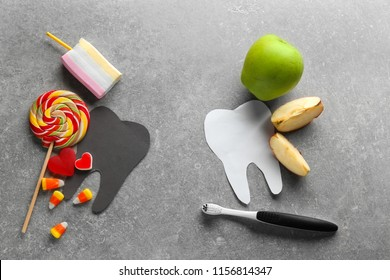 Composition with molar teeth, healthy and unhealthy food on grey background