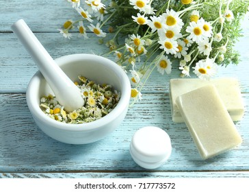 Composition with mortar, soaps and chamomile flowers on wooden table