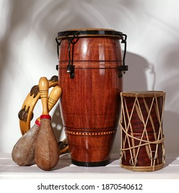 Composition of musical ethnic instrument. Maracas, tambourine, conga and ethnic drum. Percussion rhytm instruments are on white background with palm shade. Cuban sound, latin culture, samba and rumba