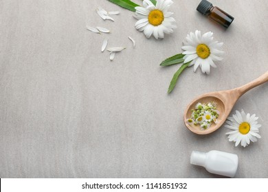 Composition with natural cosmetics and chamomile flowers on light background