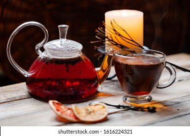 Composition with natural healthy organic herbal rooibos tea in glass teapot and cup. Wooden background, closeup. Vintage spoon and candle as rustic style decor. Atmosphere of relaxation and serenity
