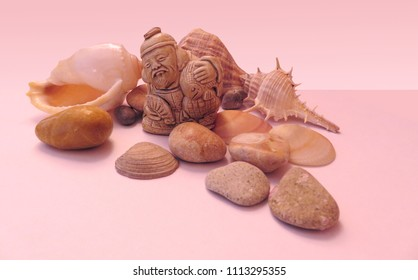 The composition of netsuke Ebisu with sea pebbles, shells and rapans