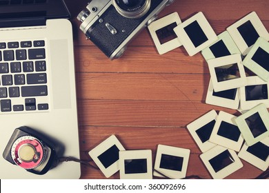 composition of old fashioned photo camera, laptop and photo slides on wooden table