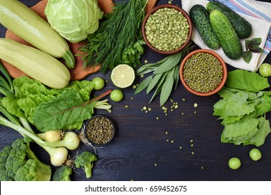 Composition on a dark background of green organic vegetarian products: green leafy vegetables, mung beans, zucchini, garlic, onions, cucumbers, peppers, lime. Top view. Green food