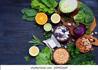 Composition on a dark background of products containing folic acid, vitamin B9 - green leafy vegetables, citrus, beans, peas, nuts, yeast. Top view. Flat lay. Healthy food
