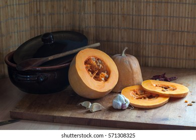 composition on the kitchen table with pumpkin, garlic, hot pepper and ceramic pots
