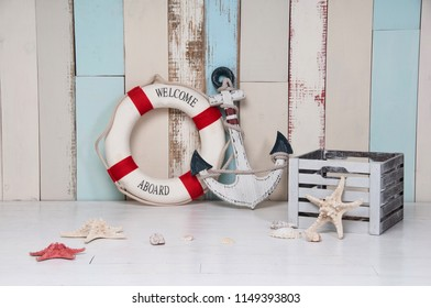 Composition on a marine theme with an anchor and life buoy, seashells and starfish on a wooden background