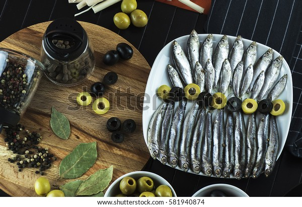 The composition on the table of the little fish, the anchovy and olives