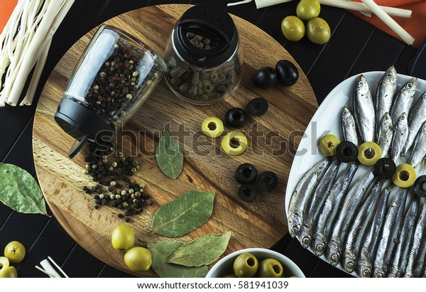 The composition on the table of the little fish, the anchovy, seasoning and olives