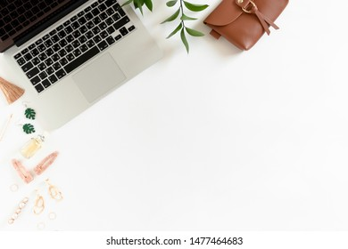 Composition on white desk with laptop, women's accessories and ruscus branch