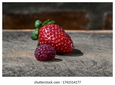 a composition on wood of strawberries and raspberriescomposition